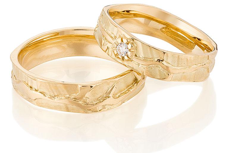 Gouden organische trouwringen met een briljant in het bloemmotief