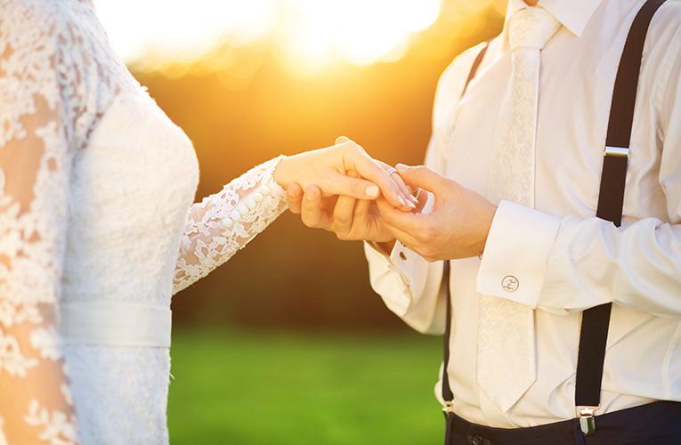 handen van bruidspaar met trouwringen om