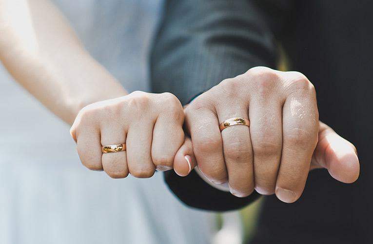 twee handen met trouwringen om de vingers