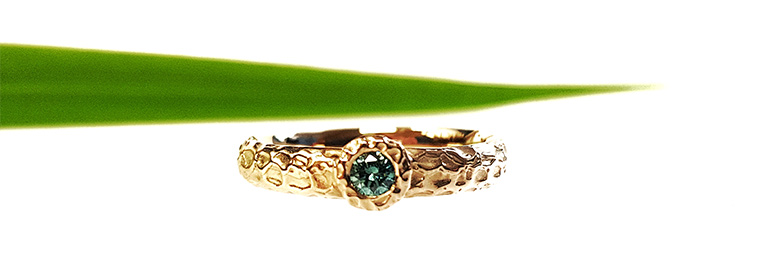 Organische ring in goud met groene briljant