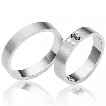 Platina trouwringen met witte en zwarte briljanten in de damesring, de herenring is mat.